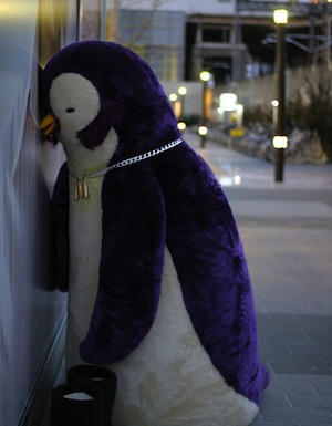 Giant toy penguin leaning against wall tired